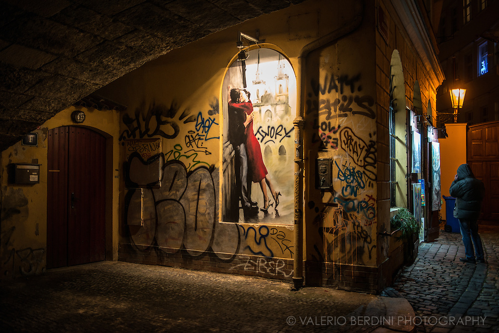 A man talks on the phone under Charles Bridge in Prague. A door is closed and a graffiti depicting two lovers is lit by a lamp.