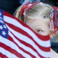 Mia McCarthy, 3 1/2, of Dorchester, looks over the top of her American flag during Memorial Day ceremonies at Cedar Grove Cemetery in Dorchester, Monday,  May 25, 2009.