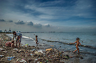 A day at the beach in Baseco slum at the mouth of the Pasig River, where these waters contain human waste, including antibiotic resistant bacteria, even heavy metals into Manila Bay.  It is hard to imagine a less healthy place to swim.  Baseco slum, Manila, Philippines.