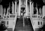 Two western men wait at the top of a temple stairs for their much younger female Thai companions to join them.  Pattaya is unmistakenly a city where much older western men with much younger Thai women is a very common sight.  Pattaya, Thailand.