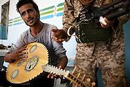 LIBYAN ARAB JAMAHIRIYA, GAZAIA : A Libyan rebel fighter plays a traditional oud instrument after rebels took control of the southwest village of Gazaia, on July 28, 2011, in Gazaia. ALESSIO ROMENZI