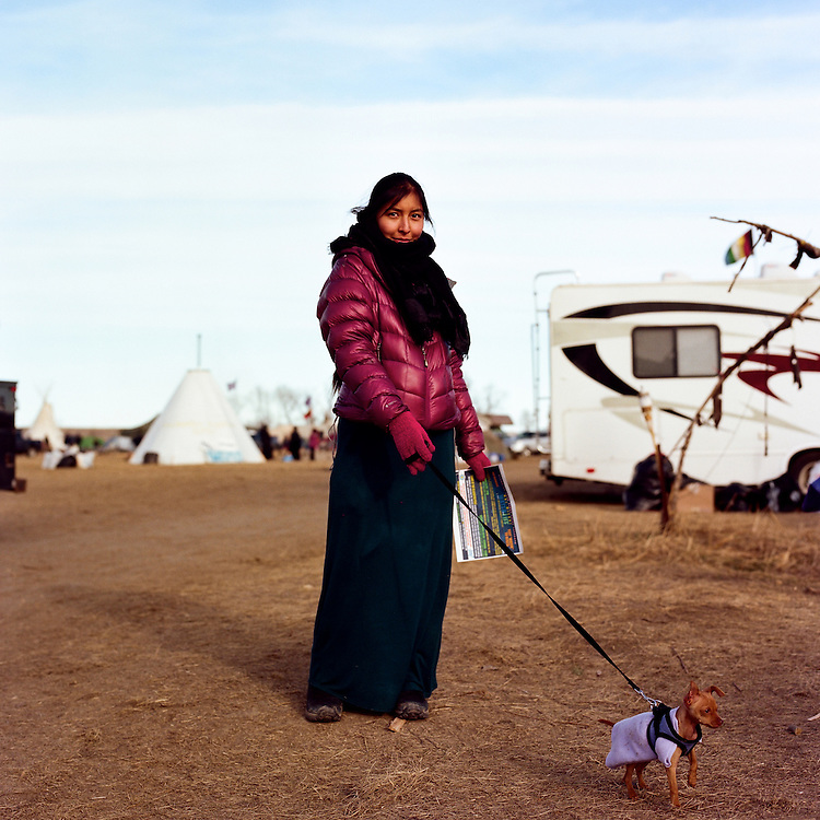 OCETI SAKOWIN CAMP, CANNON BALL, NORTH DAKOTA - NOVEMBER 25, 2016: Ruthie Edd of Colorado, Navaho, passes out fliers for an event later in the evening at the Oceti Sakowin camp in Cannon Ball, North Dakota on November 25, 2016.