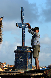 Nagapattinum, India:Jan 25:Anand, 14 years old, who lost his mother in the tsunami stands on a beach holding onto a cross  in Nagapattinum, Tami Nadu, India January 25, 2005.  Many fishermen are drinking heavily and spending all their money doled out by the government  as rumours swirl that another bigger killer wave will batter the region on January 26 and completely wash away everything that remains.(Ami vitale)