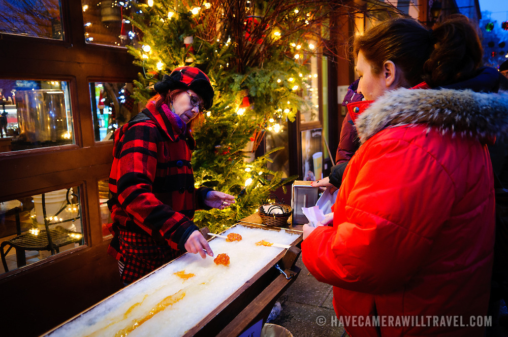 A woman makes a maple syrup taffy lollipop by rolling hot taffy in ice. The quaint old shopping street of Rue du Petit-Champlain in Quebec City's Old Town, decorated for Christmas and taken at night.