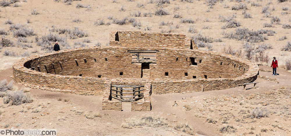 Ancient Puebloan kiva for religious rituals. Casa Rinconada, occupied about AD 1140-1200, is an isolated great kiva (out of four in Chaco Canyon), built 63 feet (19 m) in diameter with a circular inner bench, masonry firebox, masonry vaults, 34 niches, four large pits for seating roof supports, plus an unusual 39-foot (12 m) passage dug underground through sandstone and shale. Chaco Culture National Historical Park hosts the densest and most exceptional concentration of pueblos in the American Southwest and is a UNESCO World Heritage Site. Chaco Canyon is in remote northwestern New Mexico, between Albuquerque and Farmington, USA. From 850 AD to 1250 AD, Chaco Canyon advanced then declined as a major center of culture for the Ancient Pueblo Peoples. Chacoans quarried sandstone blocks and hauled timber from great distances, assembling fifteen major complexes that remained the largest buildings in North America until the 1800s. Climate change may have led to its abandonment, beginning with a 50-year drought starting in 1130.