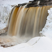 Upper Tahquamenon Falls, framed by winter ice, drops 48 feet (14 meters) in Tahquamenon Falls State Park in the upper peninsula of Michigan. The upper falls are more than 200 feet (60 meters) across and portions of the waterfall freeze in winter. The water of the Tahquamenon River appears brown or red because of tannic acid that results from the organic material generated by the cedar, hemlock and spruce forests along the river.