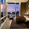 Bedroom of a Luxury high-rise condominium overlooks city and a colorful sunset