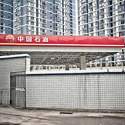 CHONGQING - JAN 18 2011: Urban view in the Jiulongpo district. A PetroChina distributor merges with the modern building on the background and a tiled wall on the front.
