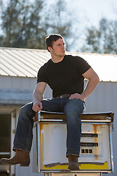 sexy man sitting on an abandoned gas pump