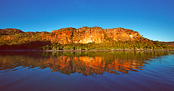 The afternoon sun lights up the stunning red cliffs of the Hunter River on the Kimberley coast.