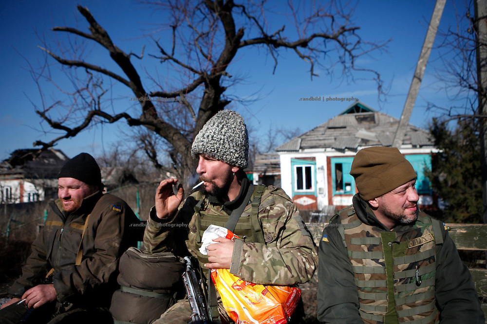 Soldiers of ukrainian armed forces on a transport through destroyed village nera the frontline of Donetsk. <br />