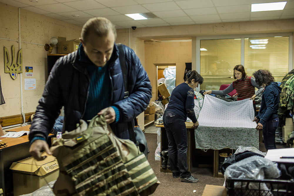 DNIPROPETROVSK, UKRAINE - NOVEMBER 16, 2014:  Edward Markovich, 43, an electrician, left, holds one of about 150 homemade flak jackets as Tanya Volynets, 46, a lawyer, Yana Sobolenko, 39, an engineer, and Lyudmyla Makaida, 48, a designer, from left, cut fabric to make underwear at the Dnipropetrovsk Volunteer Logistics Center, a charity organization that produces supplies for pro-Ukrainian fighters battling rebels in the country's East, in Dnipropetrovsk, Ukraine. CREDIT: Brendan Hoffman for The New York Times