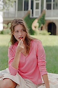 woman at a picnic eating a strawberry