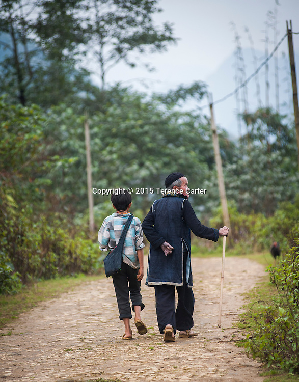 A hilltribe man and his grandson make their way home to his village after visiting the markets of Sapa, Vietnam.
