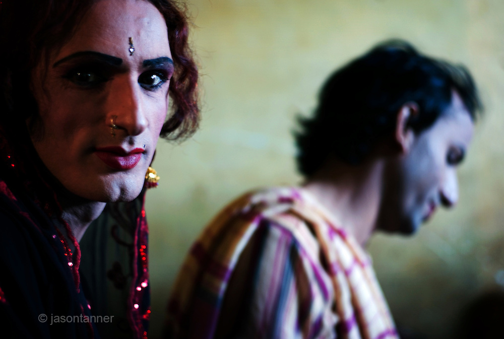 Reema, a 35 year old Hijra (near) and Sonya (background) rest before leaving for the evenings work on the streets of Karachi...The word Hijra is an Urdu word meaning eunuch or hermaphrodite. However, most Hijras in Pakistan are gay men who leave home to join the Hijra community as young boys where there is more acceptance. Most identify themselves as more feminine then masculine and dress and act accordingly...Although tolerated in a country where homosexuality is against the law, Hijras are largely ostracised from society. They are often denied work opportunities, rejected by most families, lack formal education and live in poorer areas of the city...They share similarities with the more famous Hijra communities in the Indian subcontinent and Bangladesh. In a continent where great emphasis is placed on one's ability to have children, those who are unfortunate not to be able to conceive children are not considered a true man or woman. Life for many Hijras in Pakistan consists of begging for alms (Zakat) in the more prosperous areas of the city as well as slums in addition to receiving alms when bestowing blessings on male babies and at weddings....Most Hijras dress as women, and engage in activities such as dancing and entertaining in public - activities that would be considered inappropriate for women of the subcontinent. Some members of the community engage in prostitution. .