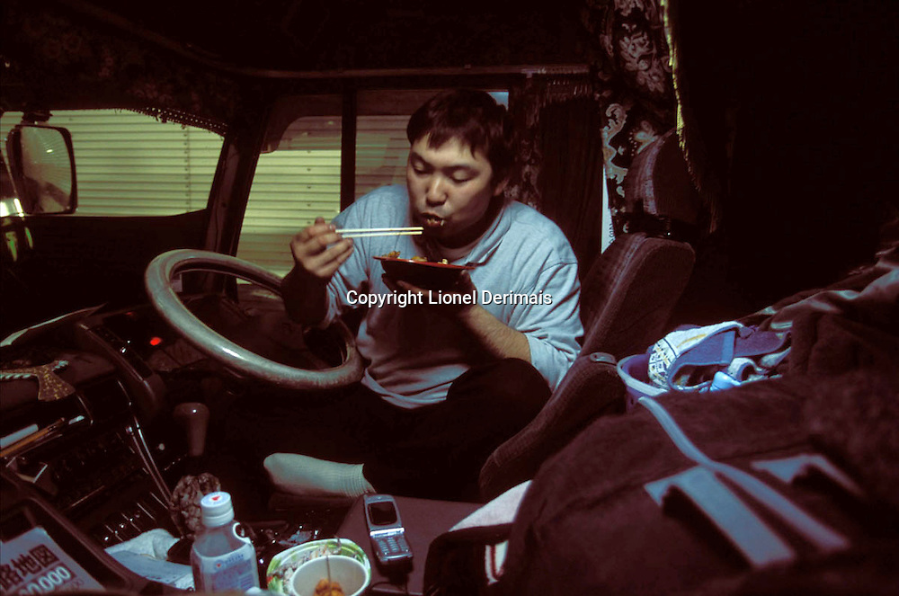 Nobuyuki eats his dinner inside the truck in the hull of a ferry during the four-hour ride between Hakodate and the Northern tip of Honshu.