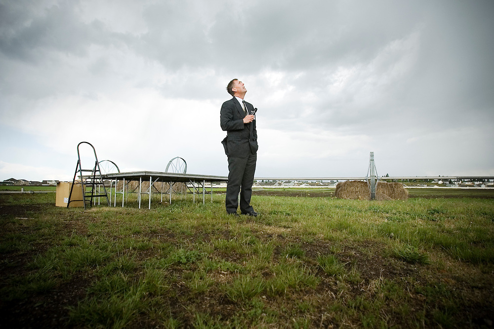 JEROME A. POLLOS/Press..Jerry Keane, Post Falls School District superintendent, looks up at storm clouds before starting a ground breaking ceremony Tuesday for a new elementary school in Post Falls. Students and other attendees took shelter inside a school bus as a hail storm postponed the ceremony.
