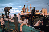 Sharjah, United Arab Emirates. Sailors reposition their dhows along the corniche