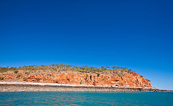 Dramatic red cliffs line Munster water at the mouth of the Prince Regent River.
