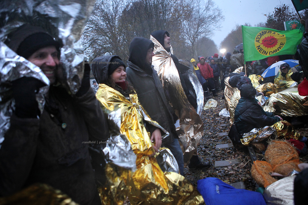 After four farmers locked themselfs on a concrete pyramide placed on the tracks usued for a nuclear waste transport to Gorleben, several hundred people have taken the chance to start a spontaneous protest sit-in on the same tracks. Strong wind and rain did not disperse the activists who intend to stay until police will bring them beside the tracks.