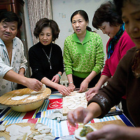 BEIJING, 25. JANUARY, 2009 :   Mr. Li (L), a paper factory owner, prepares traditional dumplings with his   relatives   on new years' eve  in Beijing .<br /> Mr. Li, a paper factory owner, is facing one of his most difficult times .&quot; Last November the market suddenly went down ,&quot; Li says.   <br /> He had bought paper, a lot of paper, and paid 7000 Yuan/ t .<br />  Li's company buys paper from paper mills and lives from the sales to publishing houses and other companies.  Since the market's collapse , he manages to sell the paper only for 6000 Yuan/t.<br /> His clients' export business to the USA had shrunk in Southern China. Mobile phone manufacturers don't need paper for the instruction guides to their mobile phones anymore as their US clients buys less China- made mobile phones.<br />  Toy manufacturers don't need paper anymore  because Americans import less toys from China. &quot; The crisis has driven many of my clients into bancruptsy&quot;, says Li.<br />  <br /> China's Communist Party  which will celebrate its 60th anniversary in October, currently faces its biggest challenge since the beginning of the economic reforms 30 years ago  : &quot; The phase of  rapid economic growth is over. For the first time the government is threatened with a  mistrust of a wide section of the population&quot;, warns the Communist party's Shang Dewen in Beijing.   <br /> Not only the China's poorest worry about the furture, but as well China's middle class is concerned about the crisis.     1,5 Millionen university graduates didn't find a job until the end of 2008  and this summer there'll be an additional  6,1 Million new graduates. More than 12 percent of university graduates face unemployment in 2009.