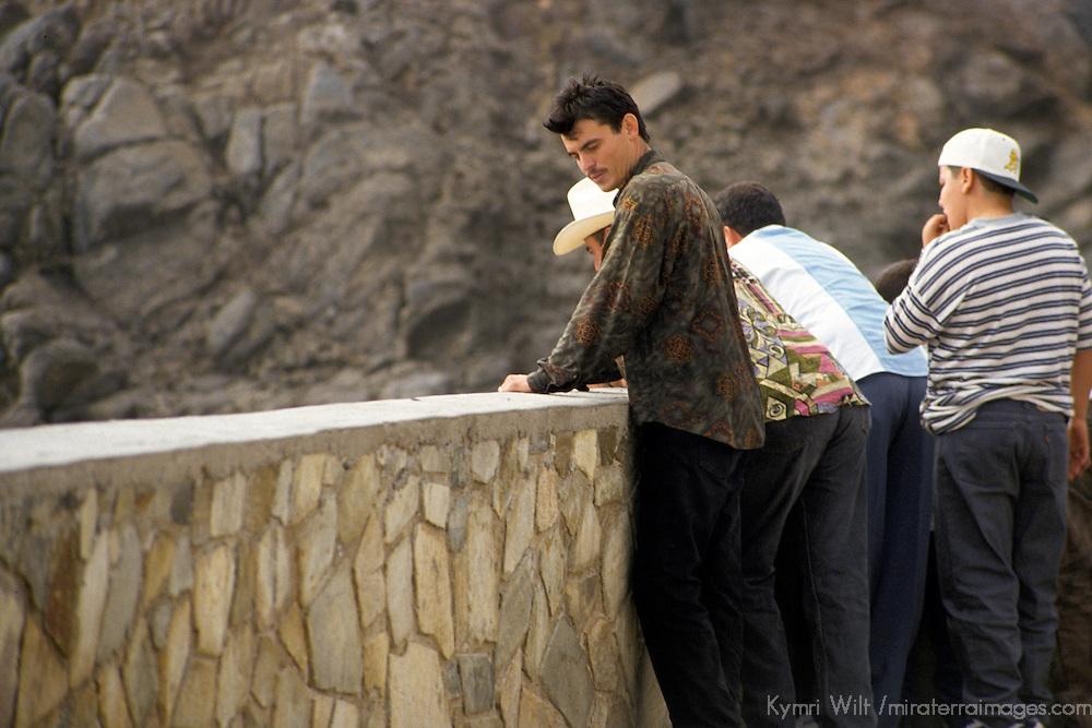 North America, Mexico, Baja California, Ensenada.  Hermanos standing at the wall watching La Bufadora.