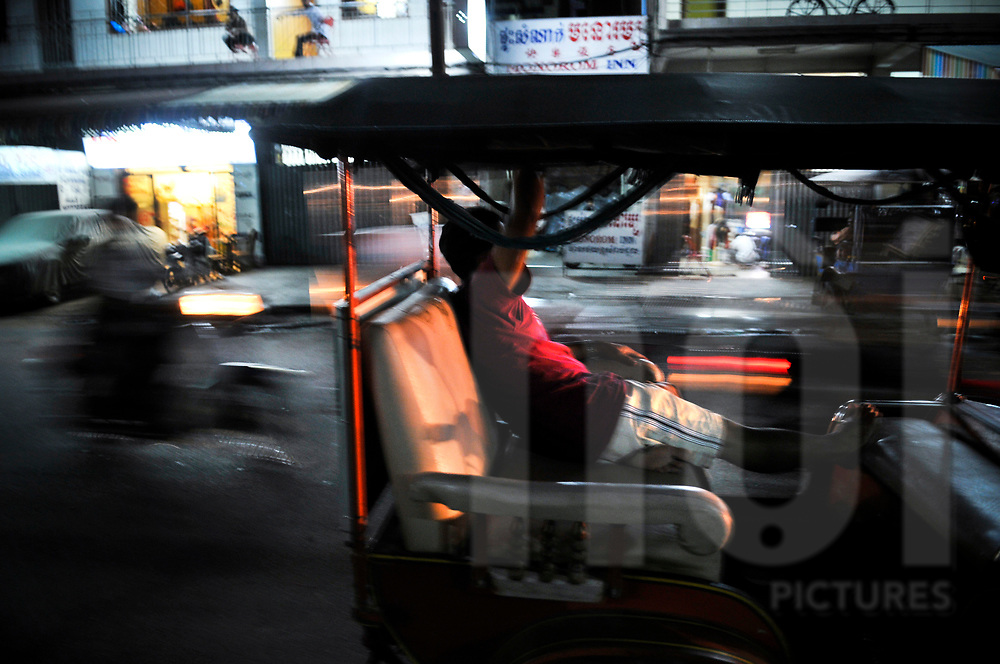 A man relaxes on the back seat of a tuk tuk in Phnom Penh, Cambodia, Southeast Asia