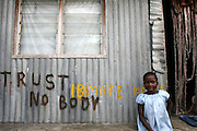 SANGANA AN OIL RICH COMUNNITY  NEGLETED.A young sits near a graffiti which says TRUST NOBODY in front of their house in Sangana, niger delta area of Nigeria,saturday Nov. 4 2006.Sangana is an oil rich but very poor community situated very close to the sea with several oil companies having their oil wells in the area.Despite it's oil and natural gas riches, the delta region remains one of the most impoverished regions of Nigeria. Delta residents accuse successive Nigerian governments and international oil companies of depriving them of the wealth pumped from their backyards.Nigeria is Africa's largest producer of crude, years of corruption and poor governance has left Nigeria's southern Niger Delta desperately poor, its environment devastated by oil spills and gas flares and other environmental hazards as a result of actIvities of the oil companies in the region. (Photo/George Osodi)