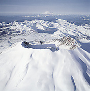 Snow encircles the crater of Mount St. Helens. The view shows nearby Spirit Lake and Mount Rainier far to the north. (Benjamin Benschneider / The Seattle Times, 2000).