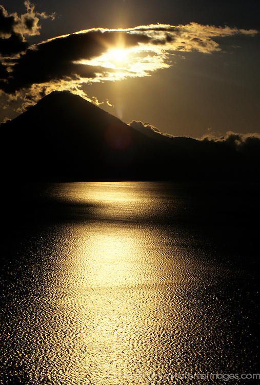 Americas, Central American, Guatemala, Lake Atitlan. A setting sun shines on Lago Atitlan in Guatemala.