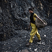 13 year old Neets Mandal digs out coal from the open cast mines in Borapahari in Jharia, Jharkhand, India.  Photo: Sanjit Das