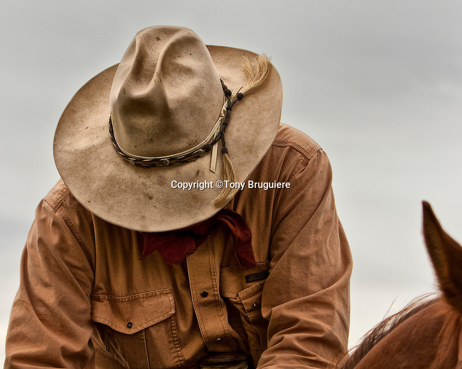 The cowboys hat is wide brimmed to protect him from the sun and rain.