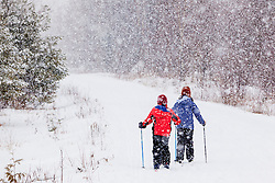 Two kids cross country skiing in a snow storm on a woods road near Greenville, Maine.