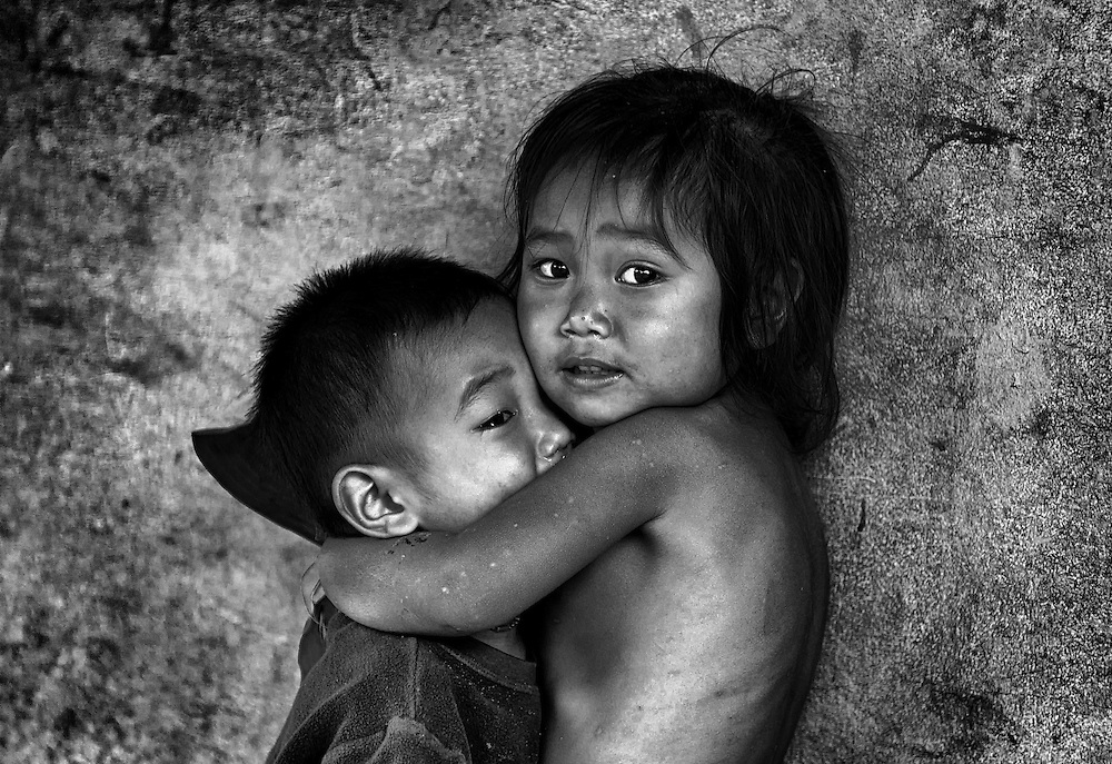 Big sister cares for her crying brother in a village near Luang Prabang, Laos.