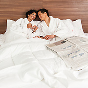 Advertising photography for Hotel Elan. Photo of couple laying in bed with breakfast and newspapers at Hotel Elan.<br /> Hair Stylist: Shannon Payne<br /> Art Director: Judith Aldama<br /> Photography: Brett Gilmour