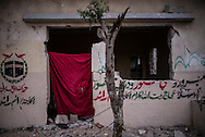 A blanket replace a door in Khuza, on the wall a graffiti rappresenting the Mecca