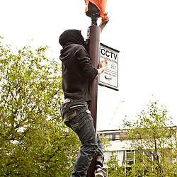 London, UK - 15 June 2012: a protester covers a CCTV camera with a plastc bag during the Carnival of Dirt. More than 30 activist groups from London and around the world have come together to highlight the alleged illicit deeds of mining and extraction companies.