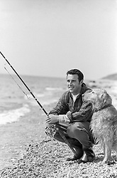 man fishing while his dog sitting faithfully next to him at the beach in East Hampton, NY