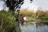 Argentina Adriano collecting water at the water source with her son Dario Antonio and her daughter Arnela Antonio, Namissimbe, Mozambique