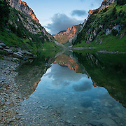 Hundstein peak reflects in Fälensee at sunrise, in the Alpstein limestone range, Appenzell Alps, Switzerland, Europe. Founded in 1903, Berggasthaus Bollenwees is a beautiful place to stay overnight in private double ensuite or dormitory rooms. A spectacular ridge walk covered in wildflower gardens starts at Hoher Kasten, reached via cable car from Brülisau, just 10 minutes bus ride from Appenzell village. For a wonderful day hike, take the lift; or arranging for overnight stay at Berggasthaus Staubern or Bollenwees allows time to ascend Hoher Kasten summit (1794 m) on foot. Appenzell Innerrhoden is Switzerland's most traditional and smallest-population canton (second smallest by area). This image was stitched from multiple overlapping photos.