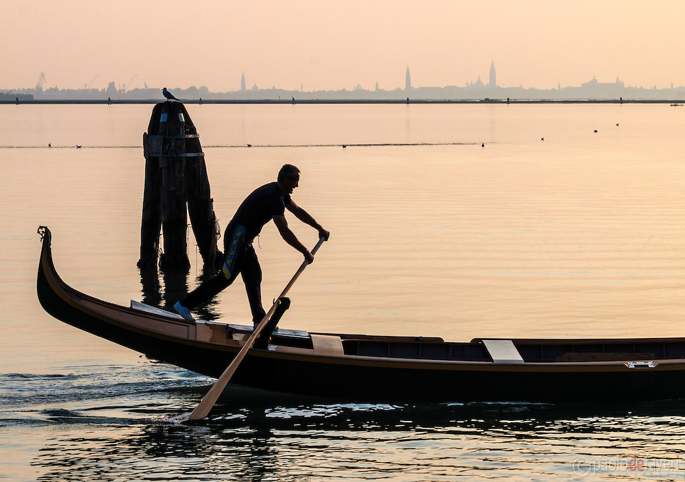 A gondolier rowing his gondola, preparing for the Regata Storica that takes place in Venice every year on the first Sunday of September. Taken at sunset from the harbour of Burano, with the skyline of downtown Venice in the background