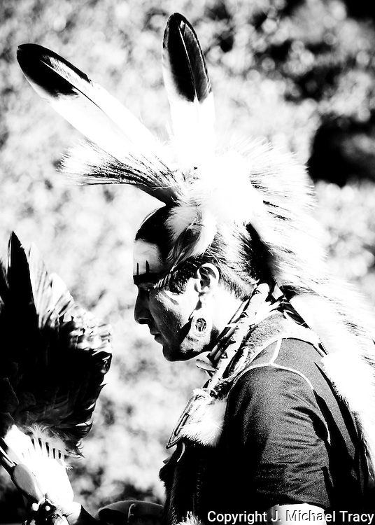 A young Native American Warrior engaged in a tribal dance, decked out in eagle feathers and traditional gear.