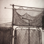 Selective focus shot of fishing nets strung over a chain link fence and gate. Shot in Little Italy area, San Diego, CA