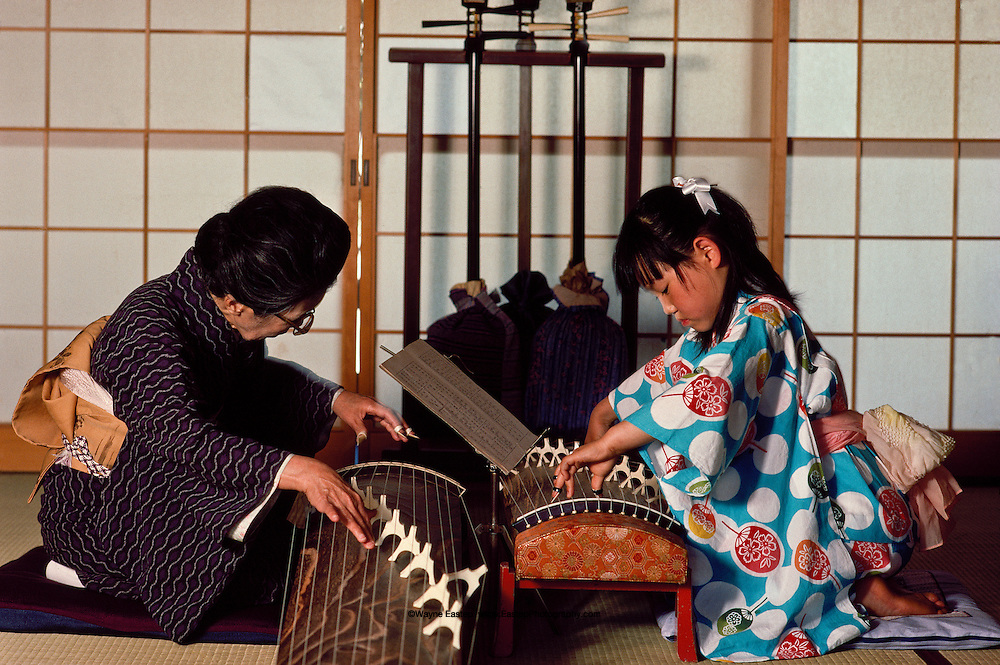 76 year old Koto teacher Toshiko Fukumori with 8 year old student Kazuko Kishimoto. The Koto is a 13 string horizontal harp a traditional Japanese instrument still popular in Kyoto. Gion district of Kyoto, Japan