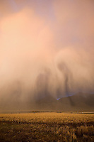 Storm Clouds illuminated by the setting sun make ghostly shapes against the backdrop of Montana's Absaroka Mountains