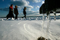 Boston, MA - Walkers make their way past a bench with icicles hanging off of it on Day Boulevard in South Boston on a frigid Sunday, January 23, 2011.  Frigid weather is expected in the region over the next few days.   Photo by Matthew Healey