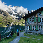 Schmadribachfall (waterfall) plunges 300 meters (1000 feet) from the lip of a hanging valley in Upper Lauterbrunnen Valley. While Schmadribachfall has been captured on canvas by noted landscape painters since the 1820s, its remote location means that more people have seen the paintings than have actually seen the falls. Directly above it to the south, the Grosshorn rises to 3754 m elevation (12,316 ft). See this view along the trail to Berghotel Obersteinberg, in the canton of Bern, Switzerland, Europe. Obersteinberg is a 2-hour walk from Stechelberg, or 4 hours from Mürren, in one of the world's most spectacular glaciated valleys. The Swiss Alps Jungfrau-Aletsch region is honored as a UNESCO World Heritage Site.