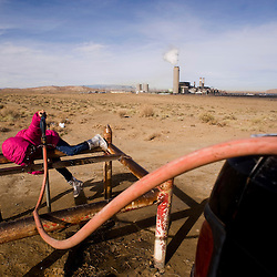 Kadin Royston plays while waiting for her family's water barrels to fill as the Four Corners Power Plant operates in the background.