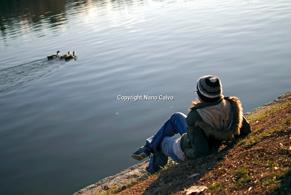 Young woman relaxing next to a lake