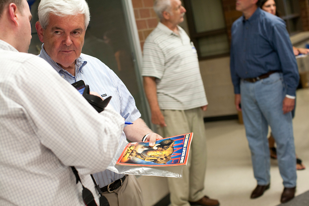 Republican presidential hopeful Newt Gingrich, second from left, speaks to an aide at a fundraiser for the Linn County Republican Party on Friday, August 5, 2011 in Tiffen, IA.